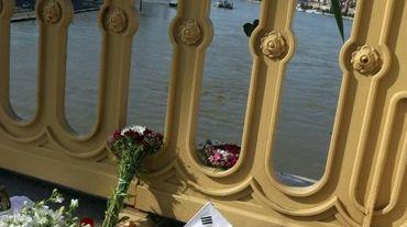 Photo prise le 1er juin 2019 à Budapest, montrant des fleurs, des bougies et un drapeau sud-coréen sur le pont Marguerite qui enjambe le Danube, au-dessus du lieu de la collision entre un bateau de croisière et une embarcation de touristes, qui a fait 7 morts et 21 disparus, principalement des Sud-Coréens.