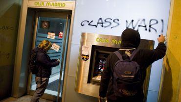 Un homme tagge le mur d'une banque en Espagne