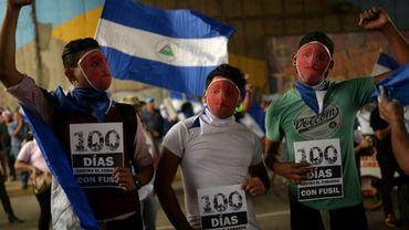 Des jeunes masqués participent à une veillée de commémoration des 100 jours de révolte contre le gouvernement de Daniel Ortega, à Managua le 26 juillet 2018