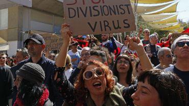 Des Chypriotes grecs se rassemblent lors d'une manifestation de part et d'autre du passage à niveau de la rue Ledra, dans le centre de Nicosie, le 7 mars 2020, contre la fermeture des passages à niveau, en raison des craintes liées aux coronavirus