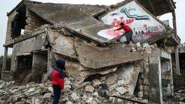 """Un homme dessine une colombe de la paix sur une maison détruite et écrit """"nous voulons toujours la liberté"""", le 13 mars 2020 à Binnich, dans la province d'Idleb, dans le nord-ouest de la Syrie"""