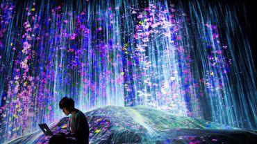 Un membre du collectif japonais teamLab près d'une cascade de lumière au Mori Building Digital Art Museum, le 1er mai 2018 à Tokyo