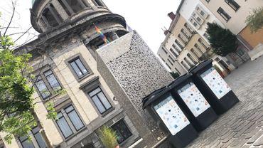 L'oeuvre d'art installée devant la maison communale et trois poubelles foncées.