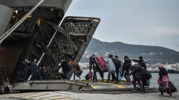 Des réfugiés embarquent à bord d'un navire de guerre dans le port de Mytilène, sur l'île de Lesbos, en Grèce.