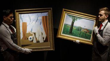 Les employés de Christie posent avec les peintures 'Le monde poétique II' (L) et 'La belle captive' (R) de l'artiste surréaliste belge René Magritte lors d'un photocall à la maison de vente aux enchères Christie's au centre de Londres le 21 février 2019 avant les trésors cachés : Chefs-d'œuvre d'une importante vente privée d'art impressionniste et d'art moderne.