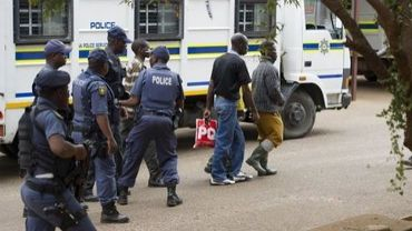 Des mineurs de Marikana accusés d'actes de violence sont escortés par des policiers dans un tribunal près de Pretoria, le 27 août 2012