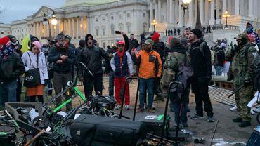 Des personnes se tiennent autour de l'équipement d'Associated Press détruit par les partisans de Trump devant le Capitole américain à Washington DC le 6 janvier 2021.