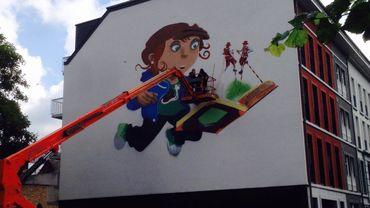 """La fresque intitulée """"Vive Nameur Pot Tot"""" représente la passation du patrimoine par l'image d'un enfant à la découverte des échasseurs."""