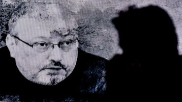 Un homme passe devant un écran projetant le portrait de Jamal Khashoggi lors d'un rassemblement en mémoire du journaliste saoudien assassiné, le 11 novembre 2018 à Istanbul