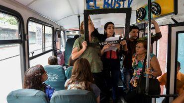 """De jeunes reporters présentent, devant un cadre en carton noir portant l'inscription  """"Le Bus TV"""", les actualités à bord d'un bus à Caracas, le 6 juin 2017"""