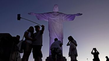 Sous la statue immense du Christ Rédempteur des dizaines de touristes prennent des selfies.