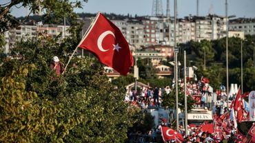 Un homme, tenant le drapeau turc, parle au téléphone, lors d'un rassemblement pour la commémoration du premier anniversaire du putsch manqué, le 15 juillet 2017 à Istanbul