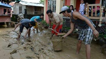 Les habitants enlèvent la boue le 20 octobre 2015 dans les rues de Cabanatuan City, au nord de Manille, apportée par les fortes pluies occasionnées par le typhon Koppu qui a fait au moins 22 morts