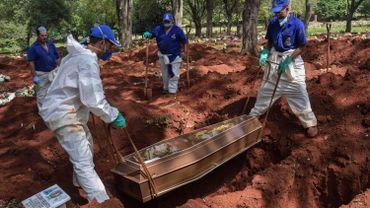 Des employés enterrent une personne qui serait décédée de COVID-19 au cimetière de Vila Formosa, dans la banlieue de Sao Paulo, au Brésil, le 31 mars 2020. Depuis, la municipalité a fait creuser 13 000 tombes supplémentaires