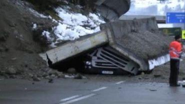 Un camion écrasé par un mur en béton après un glissement de terrain