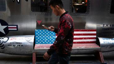 Un homme passe devant un banc décoré d'un drapeau américain devant un magasin à Pékin le 15 mai 2019