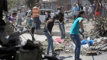 Des Libanais nettoient les rues à Tripoli après un attentat le 24 août 2013