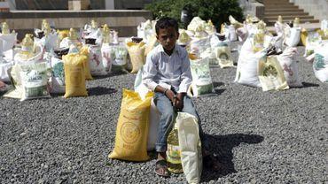 Un garçon yéménite assis sur un sac de nourriture distribué par une association locale durant le mois de jeûne du ramadan à Sanaa, le 29 mai 2017
