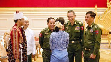 De dos, Aung San Suu Kyi, ministre des affaires étrangères dialogue avec ses nouveaux collègues militaires à la tête de la Birmanie. Sourires de circonstance ou amorce d'un véritable changement?