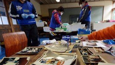 Des volontaires nettoient des photos retrouvées parmi les débris laissés par le tsunami, à Kesennuma le 10 mars 2013