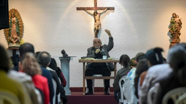 Rafael Arango, président de la Corporation Bethléem Maison Fraternelle, délivre son message assis dos au crucifix face à des dizaines de croyants de tous âges, le 2 septembre 2017 dans le nord-ouest de Bogota