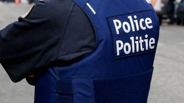 Un policier de la zone des 3 Vallées (Couvin-Viroinval) arbore deux écussons représentant une gargouille et une croix rouge sur fond noir sur son gilet pare-balles (illustration).