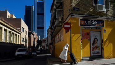 Une religieuse portant un masque de protection pousse un cabas à roulettes dans les environs de Madrid, le 19 août 2020