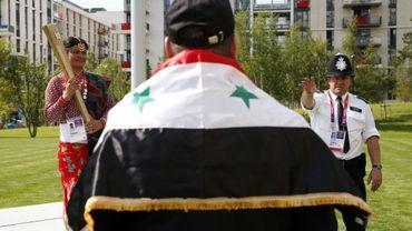 Un citoyen syrien attend pour être pris en photo avec la torche olympique à Londres