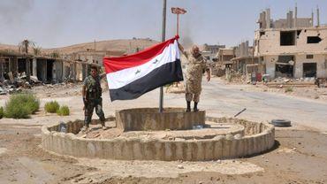 Des combattants syriens pro-gouvernementaux hissent un drapeau syrien à Al-Soukhnah, en Syrie libéré  du groupe Etat islamique, le 13 août 2017