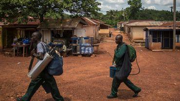 Des employés d'AGAMal (Anglogold Ashanti Malaria Ltd), chargés de pulvériser de l'insecticide contre les moustiques,  traversent le village d'Odumase, au Ghana, le 2 mai 2018
