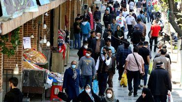 Des Iraniens, dont certains portant des masques, font du shopping dans une rue à côté du Grand Bazar à Téhéran, le 18 avril 2020