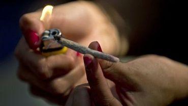 Une jeune femme allume un joint de cannabis