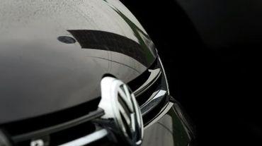 Le logo du constructeur automobile allemand Volkswagen se reflète sur une voiture Volkswagen, près du siège du groupe, à Wolfsburg (centre de l'Allemagne), le 8 octobre 2015