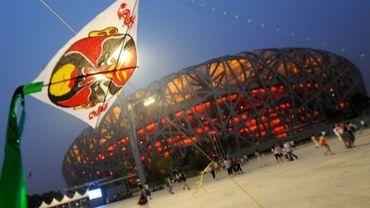 """Un cerf-volant flotte à proximité du stade dit du """"nid d'oiseau"""" érigé à Pékin pour accueillir les JO d'été en 2008"""