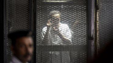 Shawkan fait le geste de prendre une photo, derrière les barreaux, durant son procès au Caire en juillet.