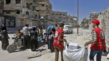 Les secouristes du Croissant-Rouge syrien distribuent de l'aide humanitaire aux habitants de Douma, dans la Ghouta orientale, le 26 juillet 2018