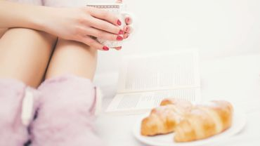 woman legs in bed, with fluffy slippers reading a book