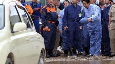 Le Premier ministre Shinzo Abe (à droite) inspecte les dégâts provoqués par les glissements de terrain  qui ont fait 52 morts et 28 disparus, à Hiroshima (Japon), le 25 août 2014