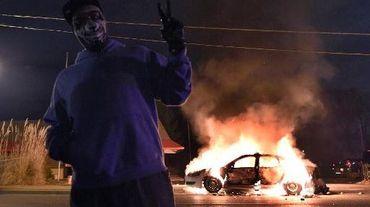 Un manifestant devant une voiture de police incendiée lors d'affrontements le 24 novembre 2014 à Ferguson