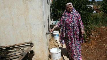 Fatma Ali, montre la fontaine de son jardin d'où aucune eau ne coule, dans son village de Salfit (nord de la Cisjordanie), le 23 juin 2016