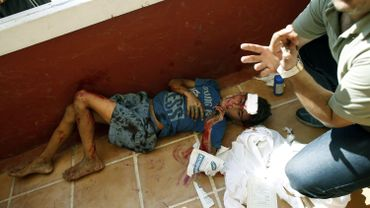 Un jeune garçon touché parmi les autres enfants blessés, soigné par les journalistes dans l'hôtel tout proche