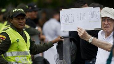 """Un homme brandit une pancarte où est inscrit """"La prison pour les FARC"""" lors d'une manifestation organisée par les citoyens et les familles de victimes des FARC, le 25 avril 2015, à Cali en Colombie"""