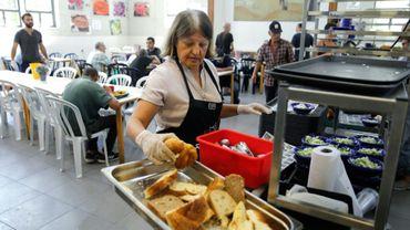 """Une femme dispose du pain sur le buffet du centre Lasova, """"resto du coeur"""" israélien, à Tel Aviv, le 8 septembre 2019"""