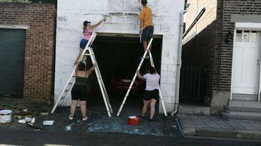 Les jeunes jobistes amaytois repeignant la façade du garage d'une habitante de la commune