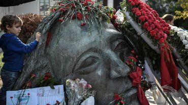 Un enfant place une rose rouge sur le monument à la mémoire des victimes du soulèvement de 1973, le 16 novembre 2019 à Athènes