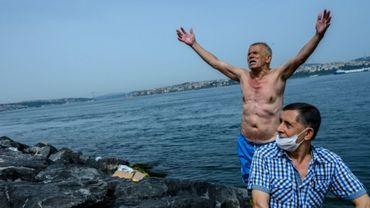Un septuagénaire lève les bras au ciel après une baignade dans le Bosphore, à Istanbul.