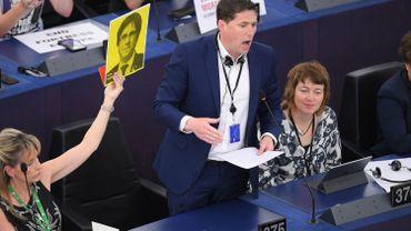 Le député européen irlandais nouvellement élu, Matt Carthy brandit une pancarte représentant le président déchu de la Catalogne, Carles Puigdemont, lors de la séance inaugurale du Parlement européen, le 2 juillet 2019 à Strasbourg.