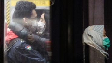Un couple s'embrasse avec des masques protection, à Hong Kong le 27 janvier 2020