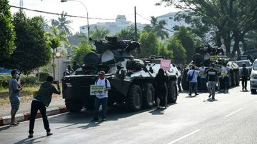 Des manifestants se rassemblent près des blindés déployés dans le centre de Rangoun, le 15 février 2021