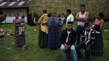 Claudia Maquin (G) dont la fille Jakelin est morte  aux Etats-Unis après son arrestation par des garde-frontières, se tient devant sa maison avec sa dernière-née dans les bras près de sa famille dans son village au Guatemala, le 15 décembre 2018